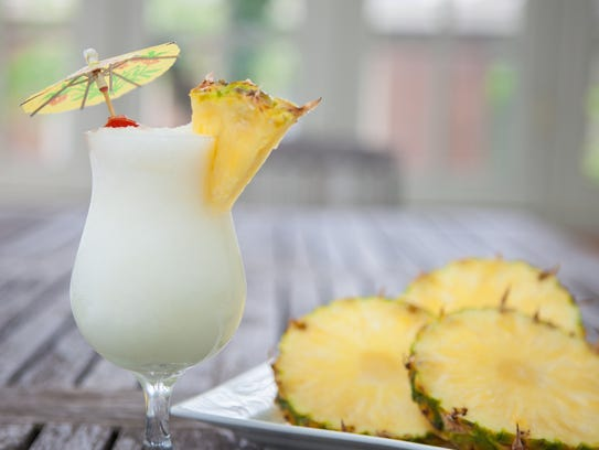 Pina Colada and Pineapple on a plate on a wooden table.