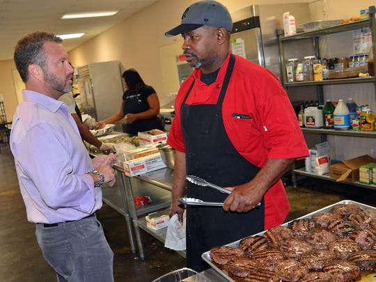 Chad Trigg, left, owner and operator of CHOW, speaks with chef Samuel Monroe about the menu for the day.