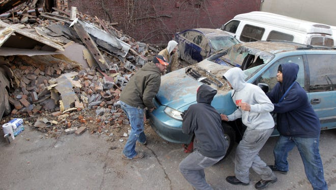 J. Combenger Custom Remodeling workers push a vehicle Dec. 27 after a building in the 100 block of West Court Street in downtown Cincinnati collapsed on it.