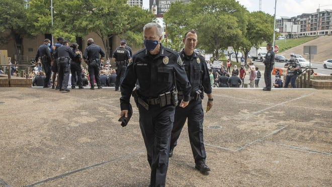 Austin Police Chief Brian Manley, left, and Chief of Staff Troy Gay walk back into the Austin Police Department Headquarters June 6 after they and other Austin police officers knelt for 8 minutes, 46 seconds in memory of George Floyd.