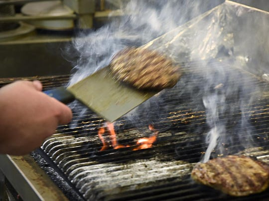 Cooks make burgers on the grill during lunch at G-Allen's Restaurant & Sports Bar Aug. 20 in Sartell.