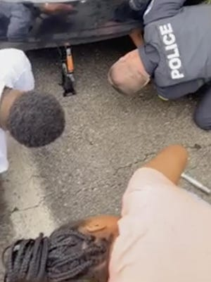Akron Police Officer James Hadbavny helps Dajha Van Dyke, 24, and her sister replace a flat tire.