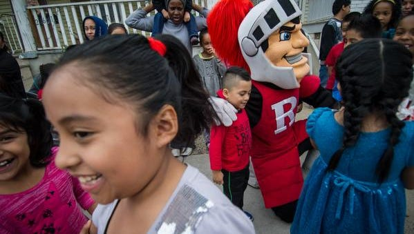 The Rutgers Scarlet Knight mascot meet and greets children waiting in line prior to the Robert Wood Johnson University Hospital and Suydam Street Reformed Church's 23rd annual Holiday Festival for children at the church in New Brunswick on Saturday, Dec.12.
