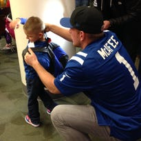 Colts punter Pat McAfee helps Nehemiah Newman strap on a backpack filled with books.