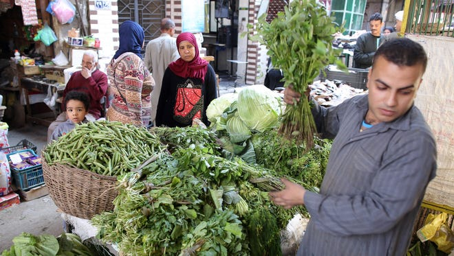 A street vendor helps customers at a market in Cairo on April 3, 2017.