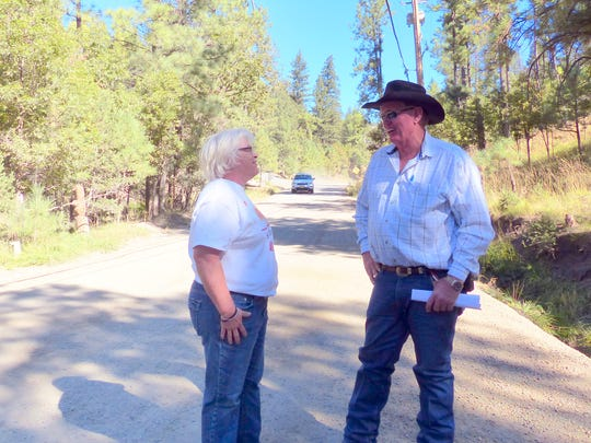 As a vehicle approaches, homeowner Melissa Corpening talks to Lincoln County Interim Road Superintendent Bill Cupit about speeding and dust problems on Musketball Drive in the Cedar Creek area of Ruidoso.
