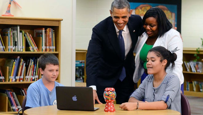 Eighth graders Sam Montgomery, left, and Alexia Martin, right, show the President Obama their math projects as he hugs math teacher Felicia Dangerfield-Persky during a tour of Mooresville Middle School in June 2013 in Mooresville, N.C. President Barack Obama says he wants 99 percent of American students connected to super-fast Internet within five years. He's directing federal regulators to use an existing program to equip schools with broadband Internet.