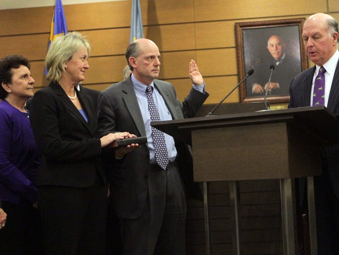 Leo E. Strine, Jr.,  is sworn in as the newest Delaware Supreme Court Chief justice by the retired Chief of Justice Myron T. Steele at the New Castle County Courthouse, Friday, February 28, 2014. Wife Carrie supports him alongside.