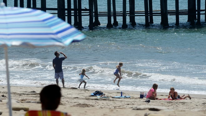 People enjoy the beach near the Ventura Pier on Tuesday as a heat wave descends on the area.