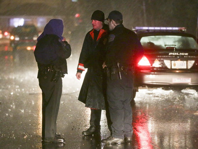 Indianapolis police officers talk during a rain storm at the scene where four people were reportedly shot on the south side, 3400 South Parker, Thursday, February 19, 2014.  Robert Scheer/The Star