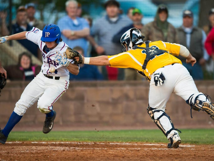 Jackson Prep's Rob Huffman (L) tries to avoid the tag of the Washington School catcher during MAIS AAA Baseball Playoff Action Wednesday in Flowood.