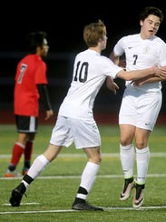 Central Kitsap soccer players Logan Field (center) celebrates with Gavin Cashmore after a Cougars' goal against Shelton on Thursday.