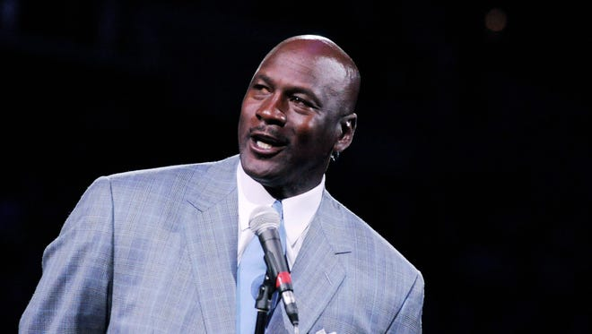 Michael Jordan unveils the new Charlotte Hornets logo at halftime during the game against the Utah Jazz at Time Warner Cable Arena.