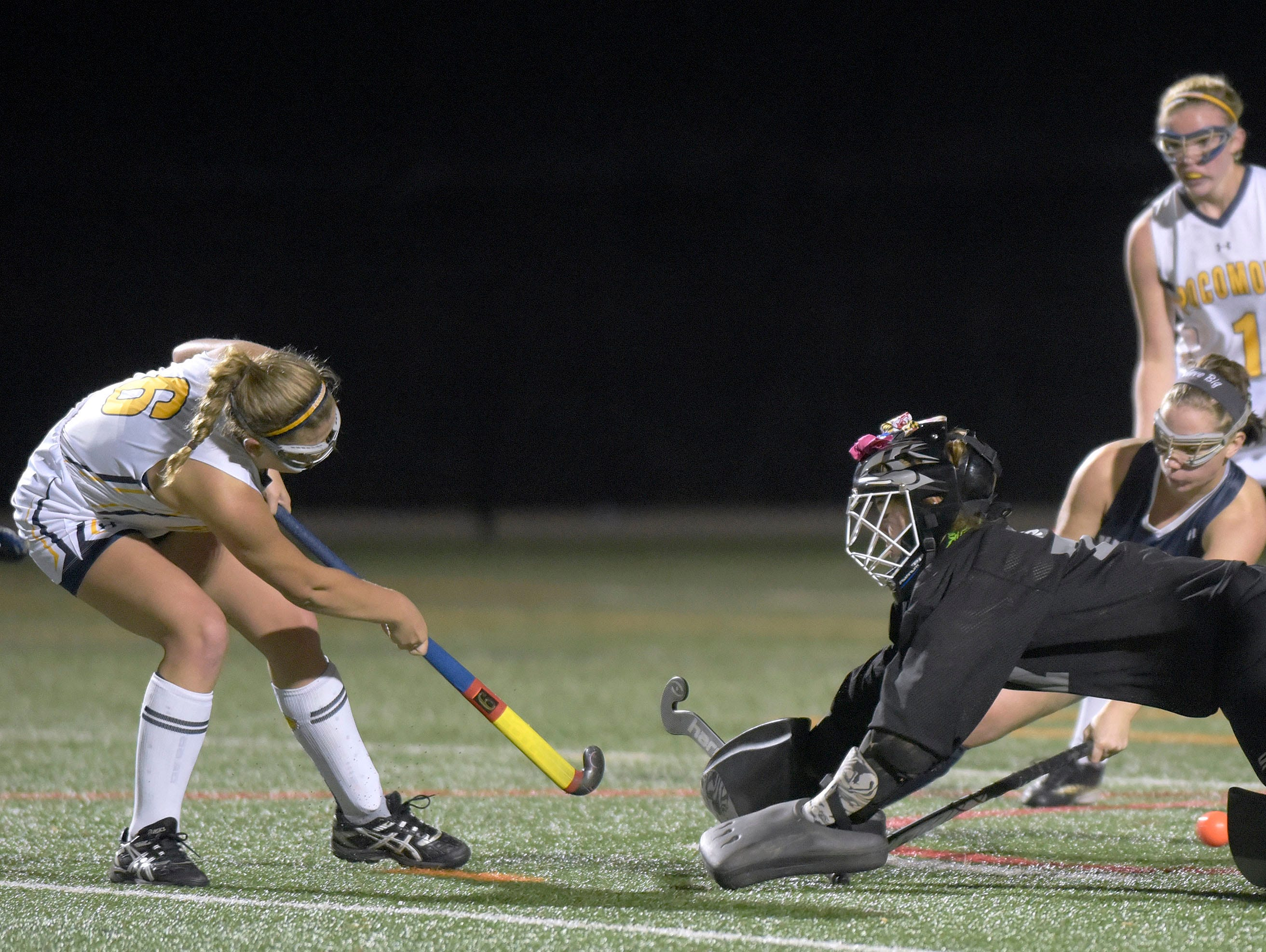 Pocomoke's Kasey Lee, left, scores against Manchester Valley goalkeeper Jacie Wood and defender Lydia Eichhorst, third from left, as Pocomoke's McKenzie Beauchamp, right, looks on in the second half of a Class 1A state semifinal field hockey game, Wednesday, Nov. 11, 2015 in Burtonsville.