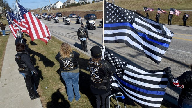 Members of the Guardian Knights line the streets to pay their respect to fallen U.S. Marshal Christopher Hill during his procession Thursday.