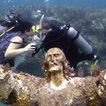 Kimberly Triolet, left, and Jorge Rodriguez, kiss after being married Aug. 25 next to the Christ of the Deep statue in the Florida Keys National Marine Sanctuary off Key Largo, Fla.