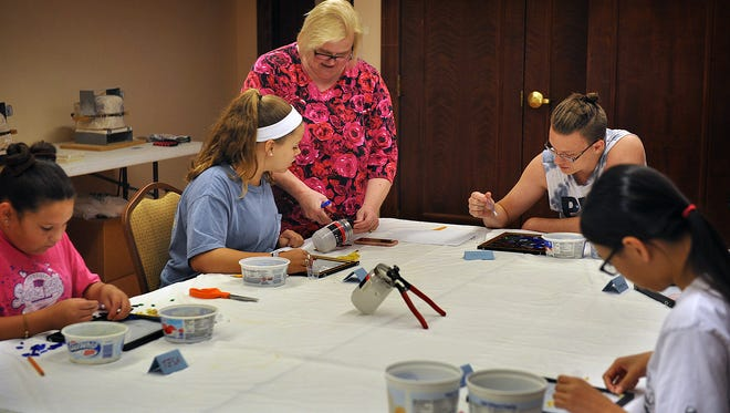 Glass artist Debbie Malone works with Presley Montz during the Awesome Glass Camp at the Kemp Center for the Arts Monday morning.