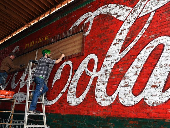 Murlal artist Michael Cooper, left, and assistant Daniel Leggett create a vintage Coca-Cola mural for a new restaurant in Nashville.