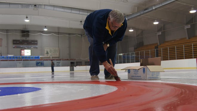 Mike Swanson paint the circles for the curling sheet for this weekend's Marsh Madness Summer Bonspiel at the SWC Recreation Center.