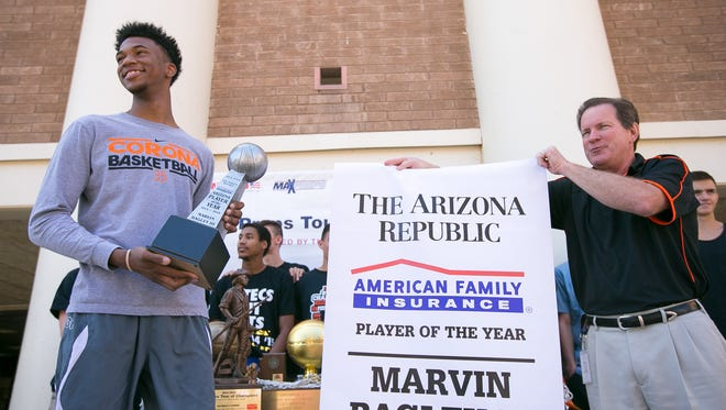 Tempe Corona del Sol boys basketball player Marvin Bagley III accepts a banner from athletic director Dan Nero for his Arizona Boys Basketball Player of the Year award at their school in Tempe on Wednesday, April 8, 2015.