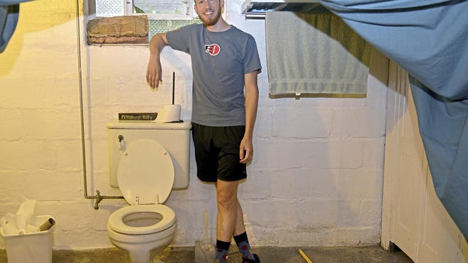 Ted Zellers stands beside a genuine Pittsburgh potty in the basement of a friend's home in the Morningside neighborhood, Wednesday, Aug. 16, 2017. He is planning a book about the bathroom phenomenon. (Pam Panchak/Pittsburgh Post-Gazette via AP)