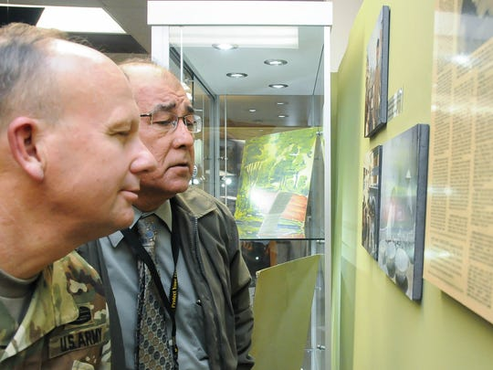 """U.S. Army Lt. Col. Don Carrothers, foreground, and WSMR Test Center deputy Frank Chavez take a close look a new exhibit at WSMR Museum titled, """"Vietnam Through a Different Lens."""""""