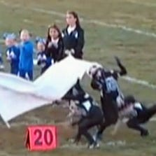 Kids in New York fall down as they run on the field