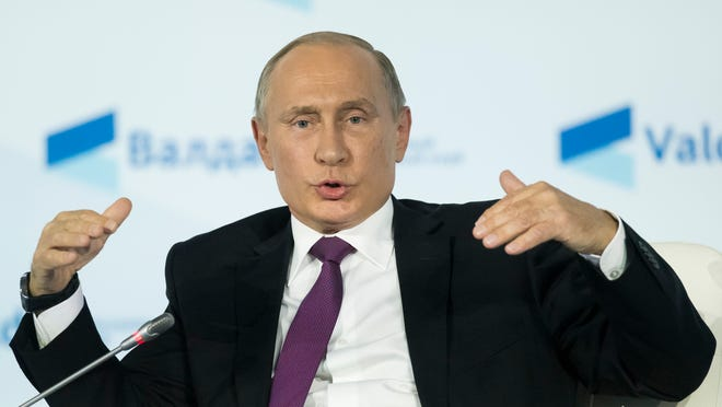 Russian President Vladimir Putin gestures while speaking at the plenary session of the an annual meeting of the Valdai International Discussion Club in the Black Sea resort of Sochi, Russia.