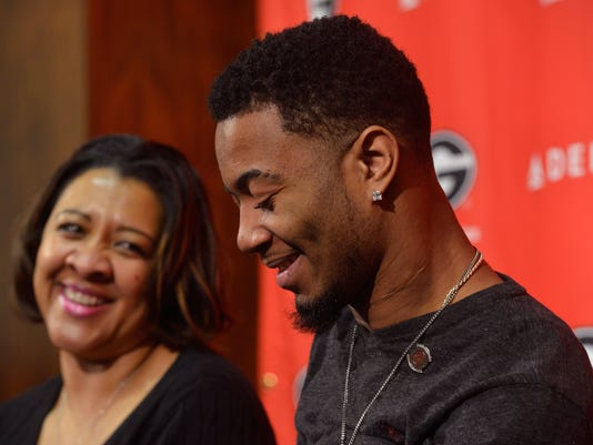 Southern University football player Devon Gales, right, laughs with his step-mother, Tanisha Gales, during a press conference on Thursday, Feb. 25, 2016,  in Athens, Ga. Devon Gales suffered a paralyzing neck injury during a September football game at Georgia. (AP Photo/Richard Hamm/Athens Banner-Herald) MANDATORY CREDIT