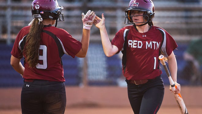 Red Mountain's Alexandra Wiley (left) high fives Tabitha Shupe after Shupe scored a run against Gilbert High during Division 1 playoff action at the Rose Mofford Sports Complex on May 13, 2014.