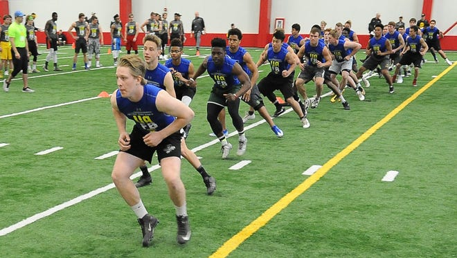 Participants in the Wisconsin Football Coaches Association prep football combine take part in warmup drills.