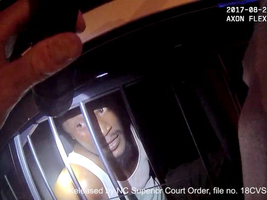 In footage from the body-worn camera of Asheville Police Department Sgt. Lisa Taube interviews Johnnie Rush in the back of a police vehicle on August 25, 2017.