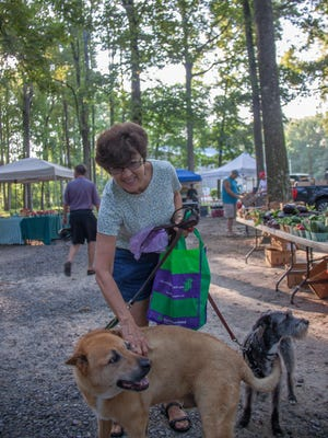 Jeannie Crust of Ocean Pines shops at the Ocean Pines Farmers Market with friends Bogey and Dixie. Saturday is a Dog Day of Summer at the market to benefit the Worcester County Humane Society.