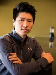 Alan Zhuo, owner of Bonfire Mongolian Grill, poses