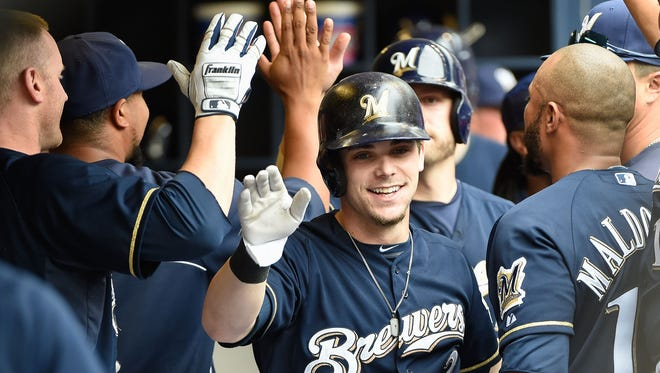 Milwaukee Brewers second baseman Scooter Gennett (2) is greeted in the dugout by his teammates after hitting a grand slam in the second inning against the Washington Nationals at Miller Park.