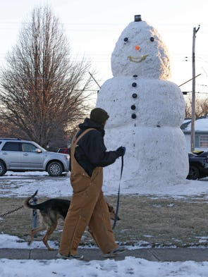Wednesday January 29th, 2014, a passerby checks out an 18ft, 1in snowman in the yard at  5017 W. 22nd St.  in Speedway. The home of brothers, Alan & Eric Burke. The brothers created the snowman using all the snow from the yard, solar yard lights for buttons and eyes, and a street cone for the nose.