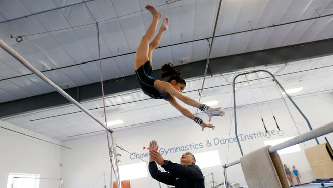 Coach Liang Chow spots Victoria Nguyen, 15, as she practices on the uneven bars Tuesday, April 19, 2016, at Chow's Gymnastics and Dance in West Des Moines.