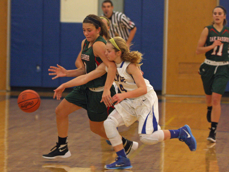 Oak Harbor's Emma Barney and Clyde's Heidi Marshall chase a loose ball Saturday.