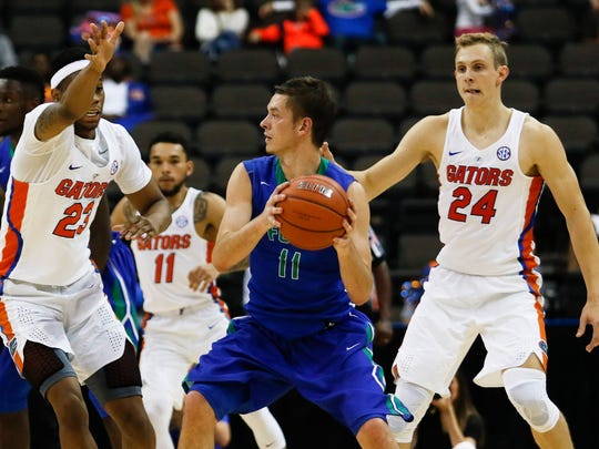 Florida Gulf Coast Eagles guard Christian Terrell (11) looks to pass the ball in the second half as Florida Gators forward Justin Leon (23) and guard Canyon Barry (24) defend at Jacksonville Veterans Memorial Arena. Florida Gators 80-59 on Nov. 11, 2016, in Jacksonville.