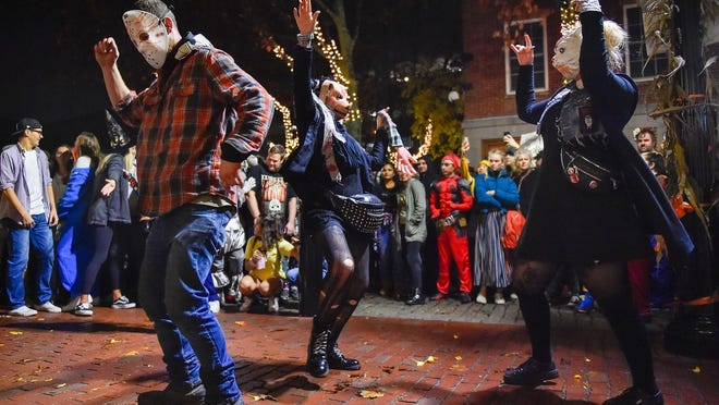 People dressed in costumes dance to drum beats from an Essex Street performer in Salem on Halloween night, Oct. 31, 2019.