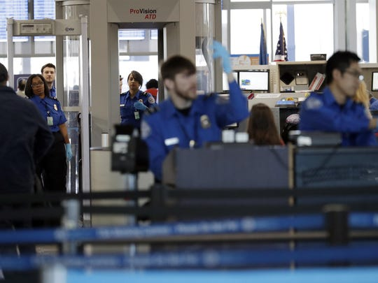 FILE- In this Jan. 5, 2019, file photo Transportation Security Administration officers work at a checkpoint at O'Hare airport in Chicago. The percentage of TSA airport screeners missing work has hit 10 percent as the partial government shutdown stretches into its fifth week. The Transportation Security Administration said Monday, Jan. 21, that Sunday's absence rate compared to 3.1 percent on the comparable Sunday a year ago. (AP Photo/Nam Y. Huh, File)