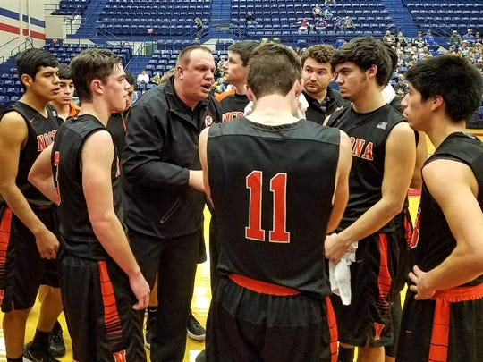 Nocona coach Bret Botard (center) talks to his team during a timeout in Tuesday's Region I-3A bi-district game against Brock in Graham.