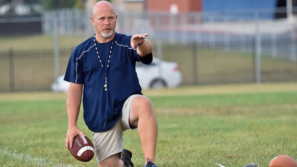 Coach Mark Luther runs drills with kicker Nazeer Taylor