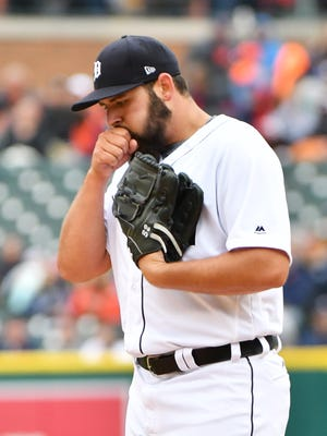 Tigers pitcher Michael Fulmer tries to warm his hand after a walk in the first inning.