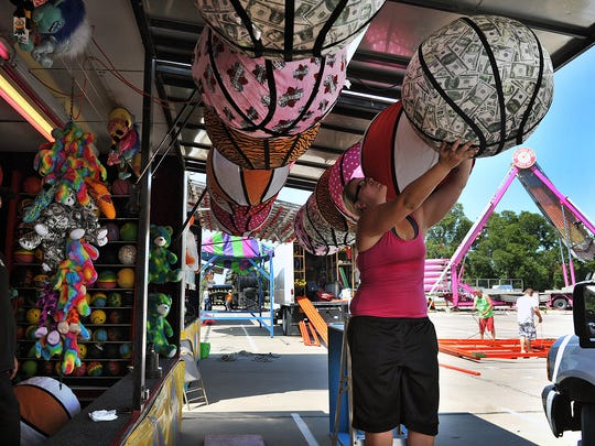 Mercedes Lundgren hangs prizes for the Mini-Ball game on the midway of the Texas-Oklahoma Fair Monday afternoon.