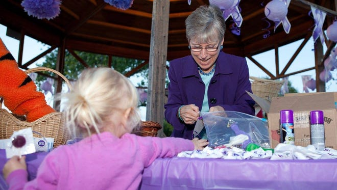 COPE Executive Director Kay Gomolak passes out bracelets honoring domestic violence survivors at their vigil last year.