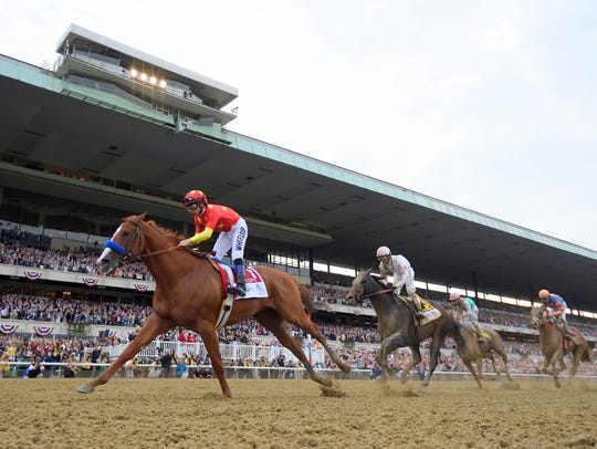 Jockey Mike Smith, left, winning the Belmont Stakes