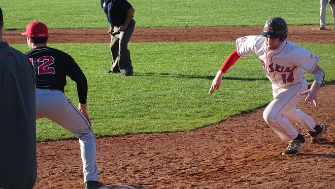 Coshocton's Andrew Mason begins to dive head first back to first base against Bishop Rosecrans.