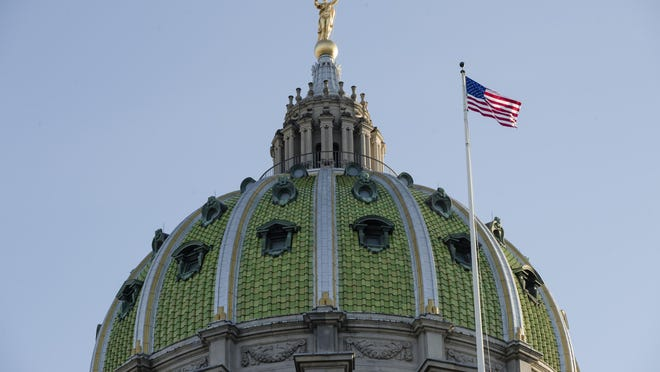FILE- In this Jan. 15, 2019, file photo an America flag flies at the Pennsylvania Capitol building in Harrisburg, Pa. In Pennsylvania, good fiscal times may not necessarily mean good fiscal condition. The rage in the state Capitol right now is the surplus that state government rolled up in the almost-ended fiscal year, helped by unexpectedly strong corporate and sales tax collections. That news alone is fueling requests from a legion of lobbyists with pet projects, but the momentary surplus has not necessarily changed views from the outside that Pennsylvania is a state with tall fiscal challenges. (AP Photo/Matt Rourke, File)