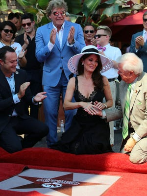 """""""Real Housewives of Beverly Hills"""" star Lisa Vanderpump thanks Palm Springs Walk of Stars president Bob Alexander moments after her star on the Palm Springs Walk of Stars is unveiled Wednesday. At left is Palm Springs City Council member Paul Lewin, and standing is Vanderpump's husband, Ken Todd."""